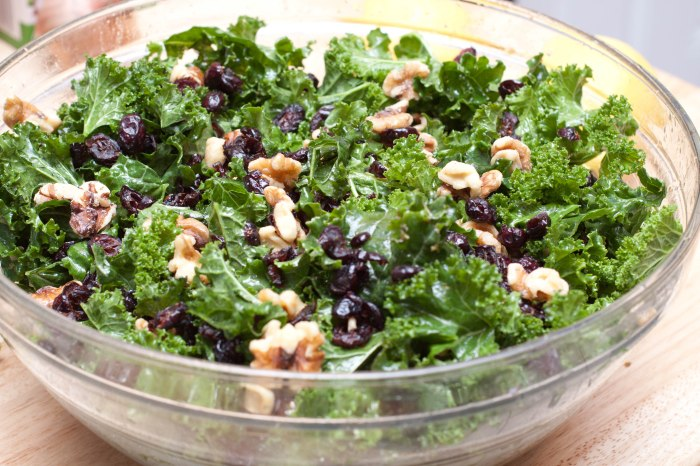a large bowl with kale, cranberries, and walnuts